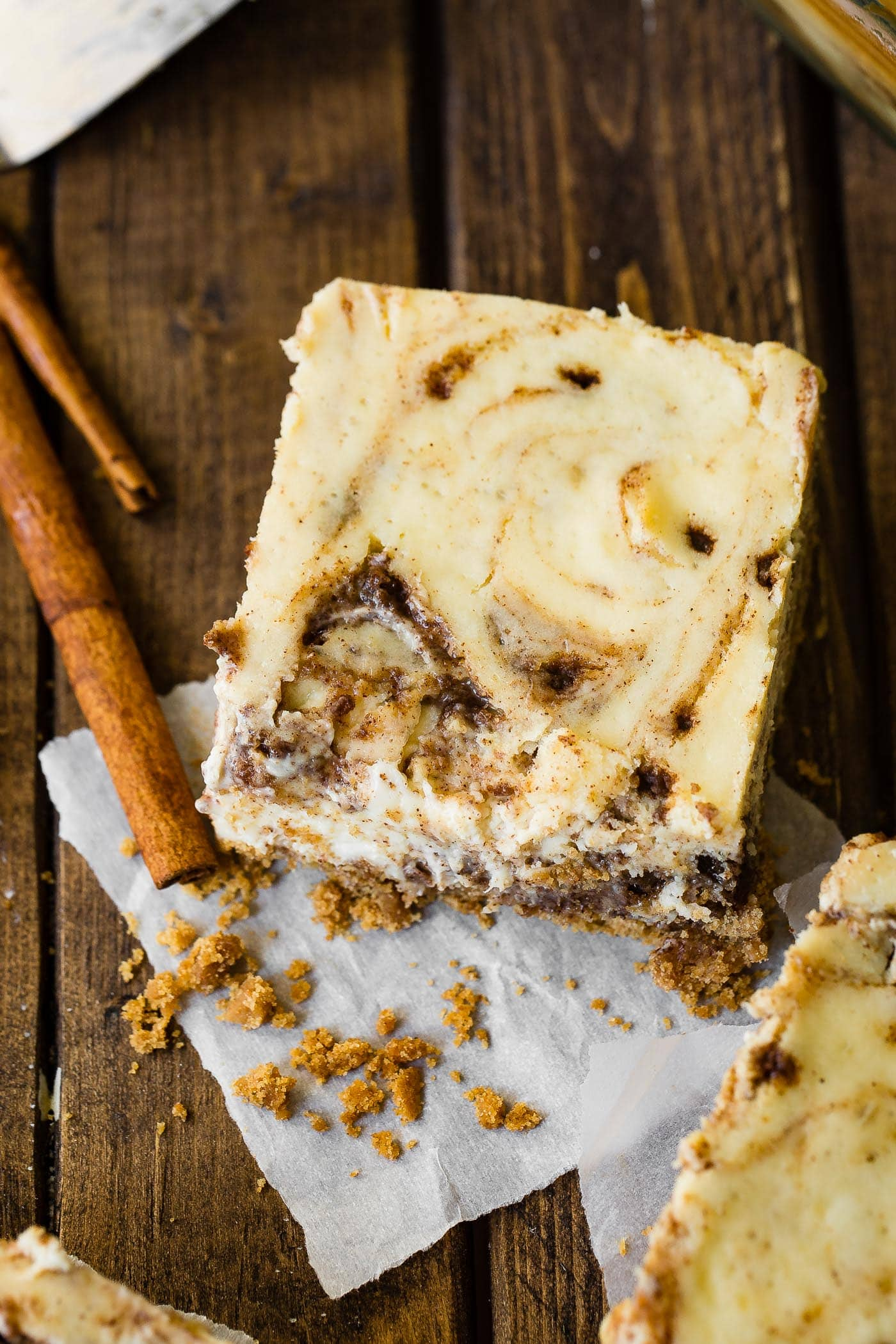 A photo of a cinnamon roll cheesecake bar sitting on a wooden surface with cinnamon sticks sitting next to it.