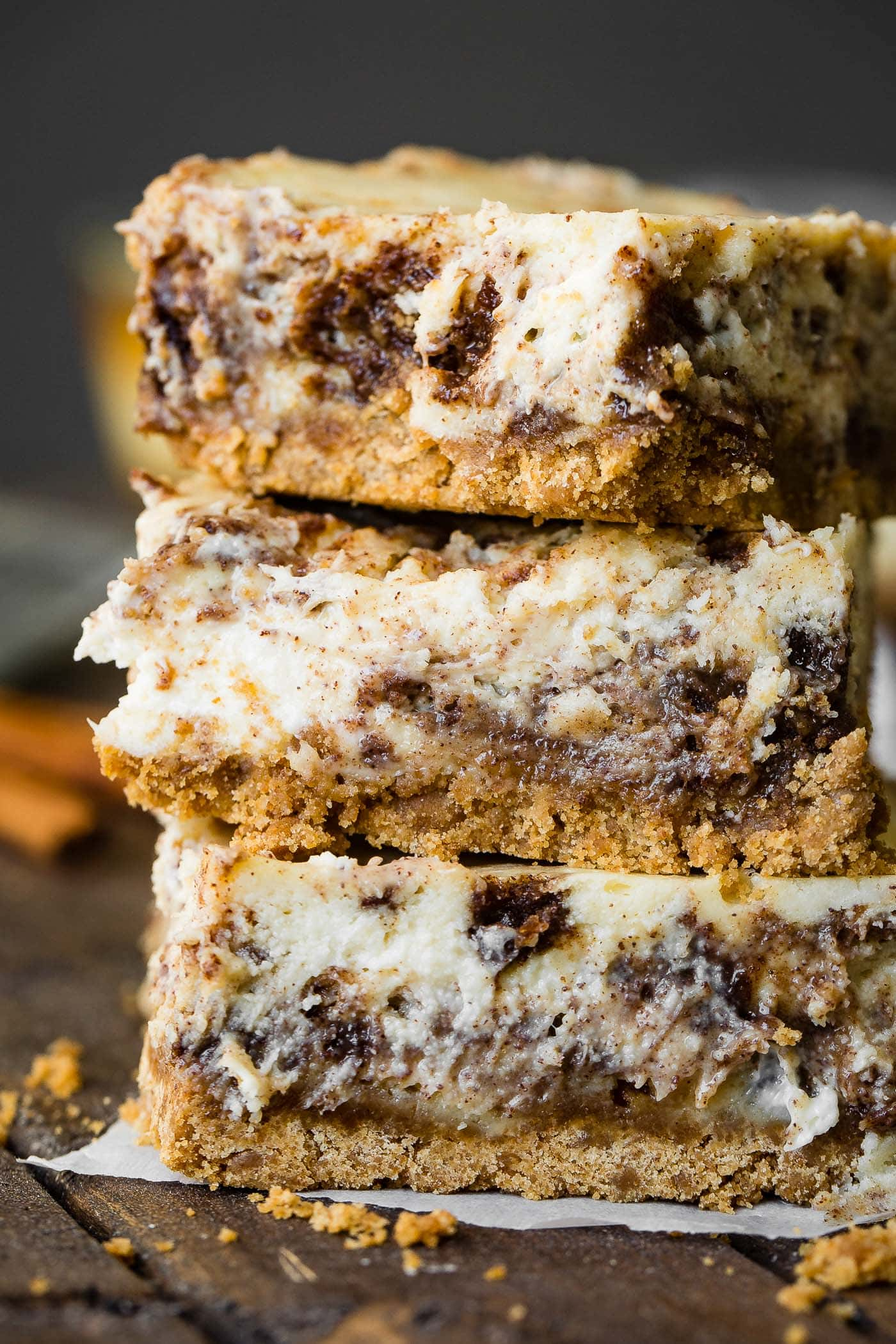 A photo of three cinnamon roll cheesecake bars stacked on top of each other.