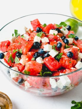A blueberry feta watermelon salad with cubes of feta cheese and fresh basil and mint leaves.