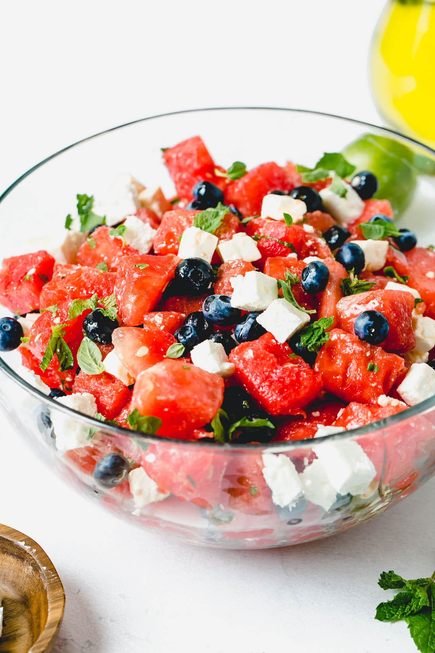 Blueberry feta watermelon salad with feta cheese cubes, fresh basil and mint leaves.