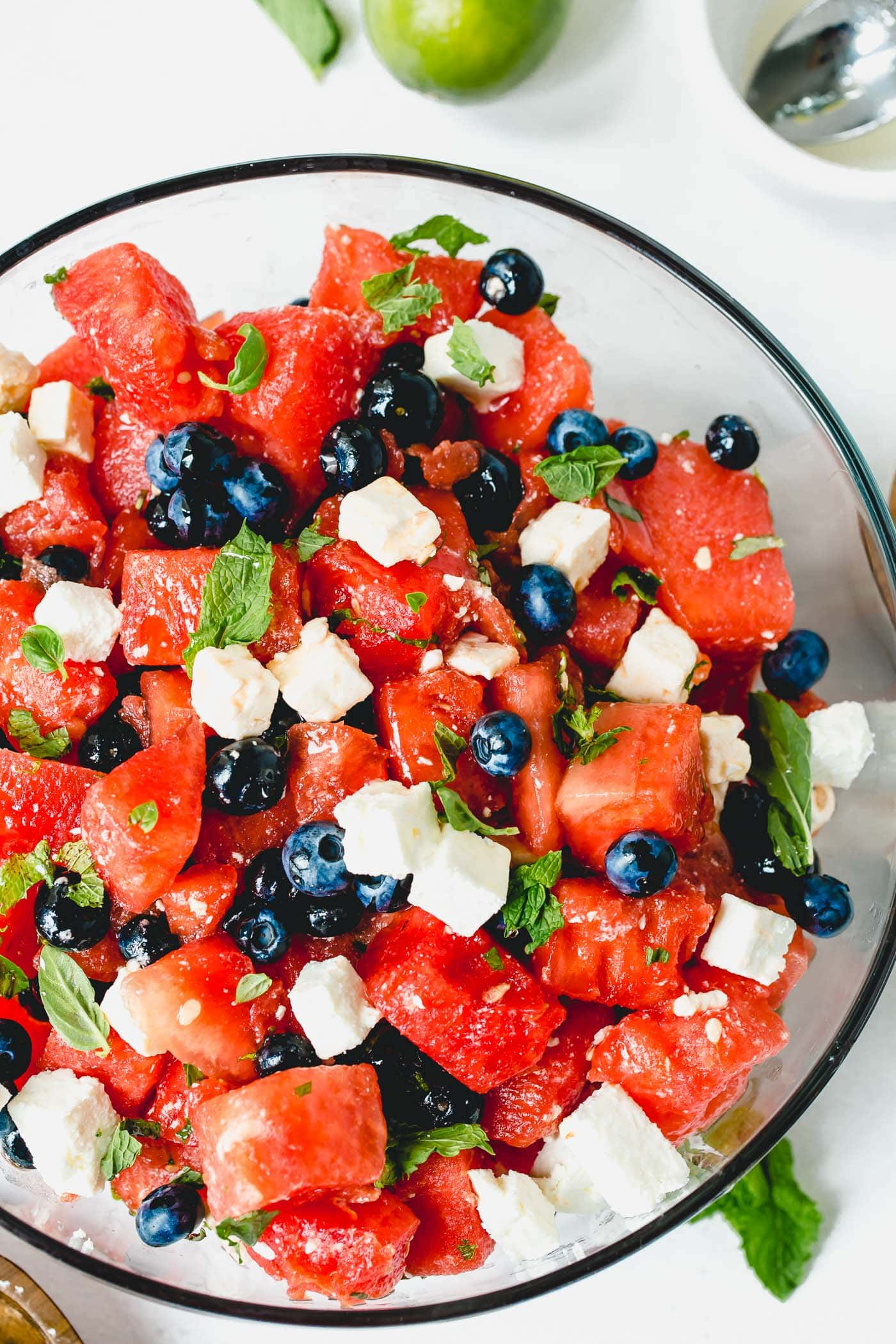 A plate of feta and watermelon salad.  Blueberries, watermelon pieces, and feta cheese cubes mixed with basil and mint leaves.