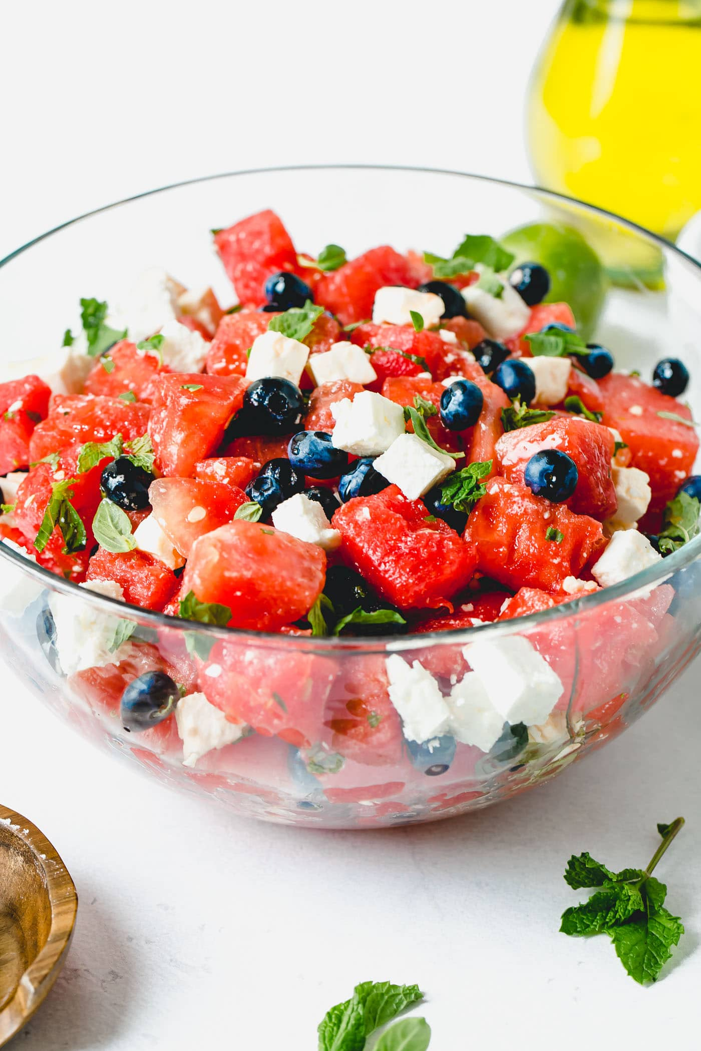Blueberry feta watermelon salad in a glass serving bowl. There are fresh blueberries, cubes of watermelon, and cubes of feta cheese mixed with a few fresh basil and mint leaves.