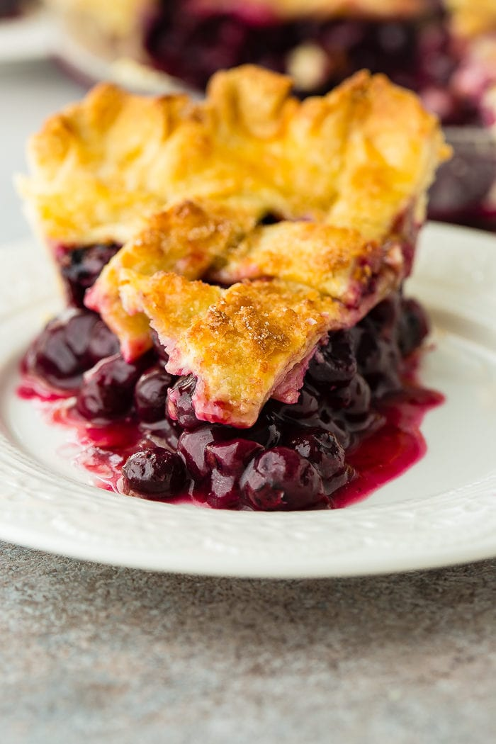 A photo of a slice of blueberry pie on a white plate.