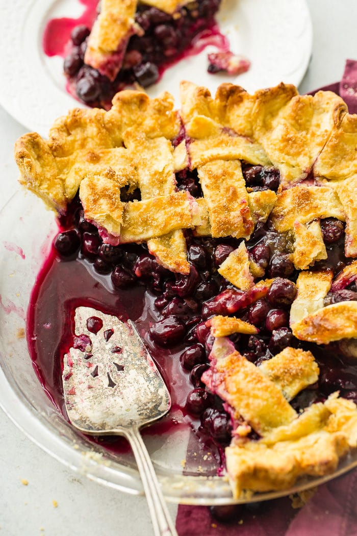 A photo of a blueberry pie with a lattice top with a couple of slices taken out and a pie server in the pan.