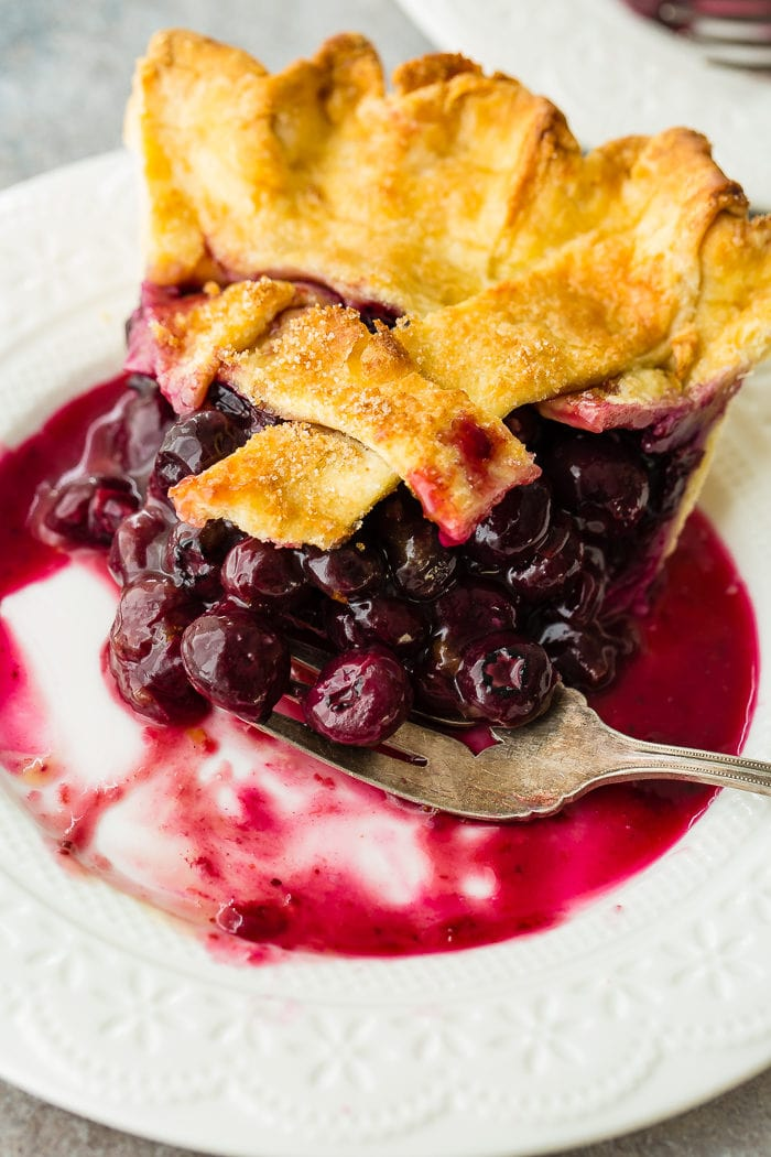 A photo of a slice of blueberry pie on a white plate with a bite taken out of it and fork sitting on the dish.