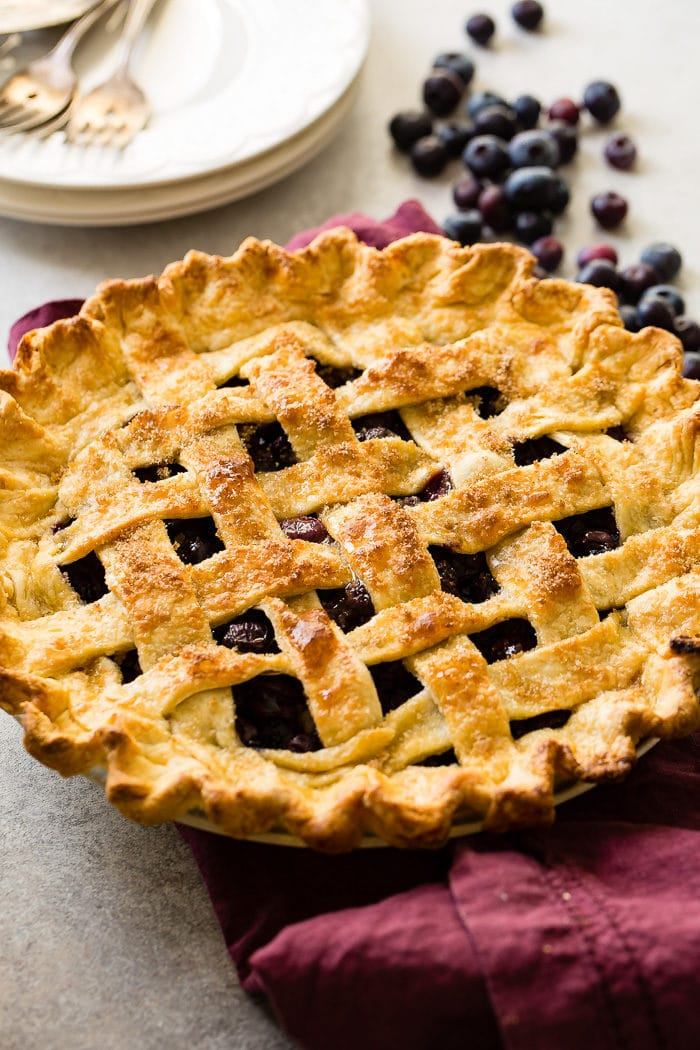 A photo of a blueberry pie with a lattice top and beautifully golden crust.