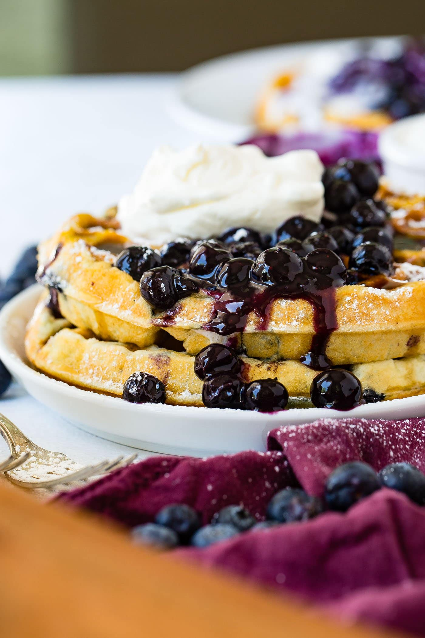 A stack of blueberry waffles on a dinner plate. There is a large scoop of blueberries on top and running down the sides of the waffles. The blueberries are topped with whipped cream. There are fresh blueberries on the table beside the plate.