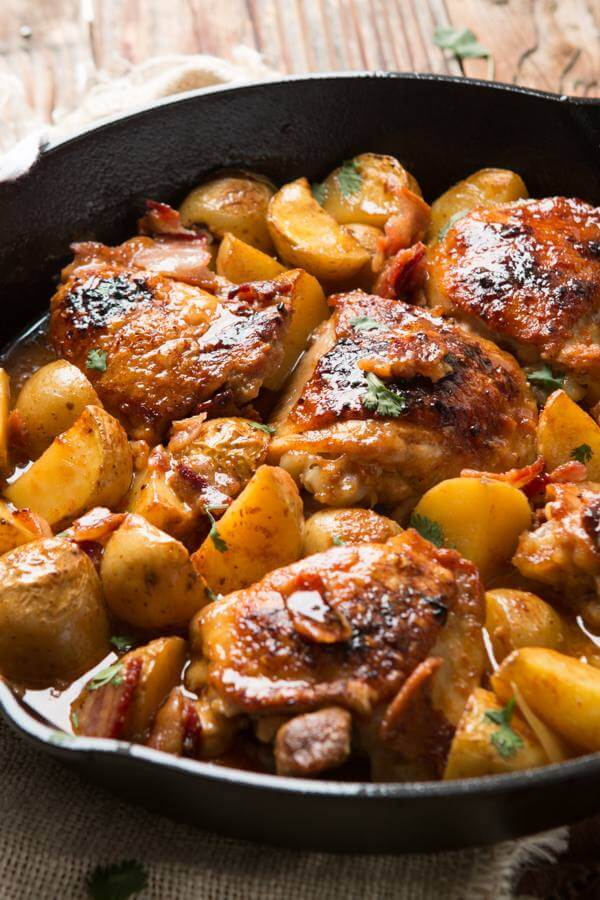 braised chicken thighs and potatoes in cast iron skillet