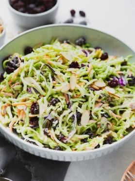 a photo of broccoli slaw in a big white ceramic bowl with slice almonds on top.