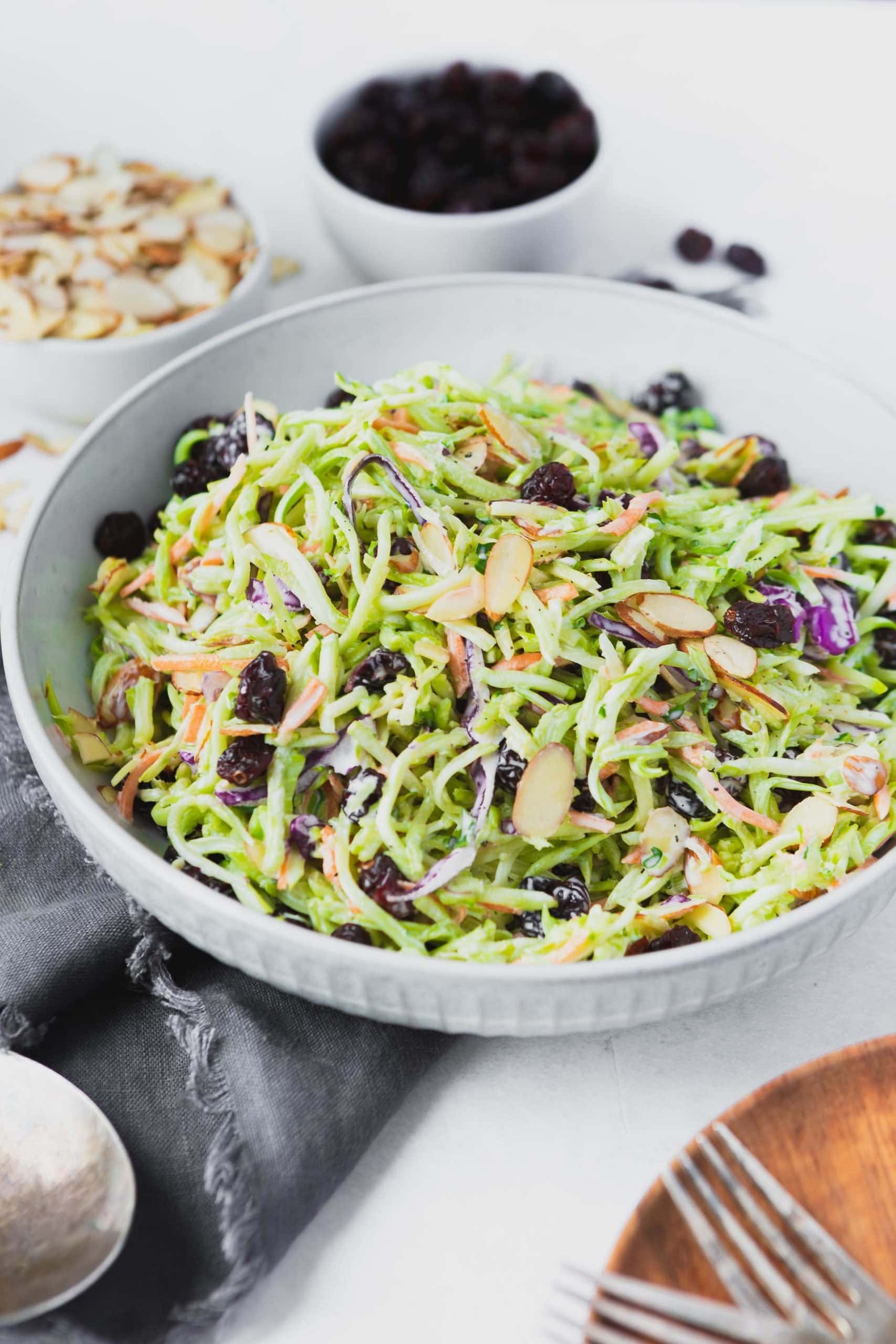 a photo of a bowl full of broccoli slaw topped with sliced almonds and plump raisins all in a large white bowl.