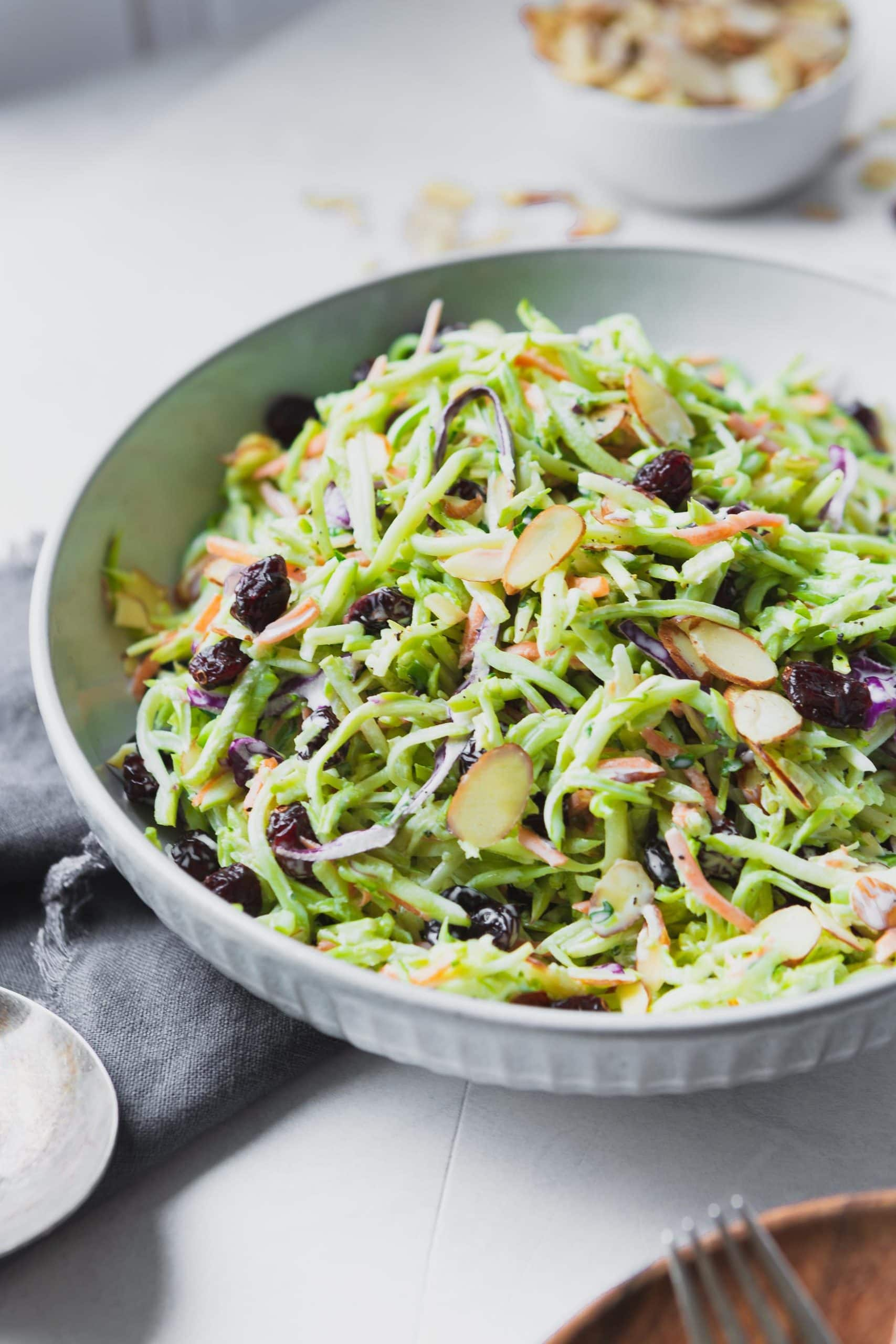 a photo of a big white ceramic bowl full of broccoli slaw topped with raisins and sliced almonds