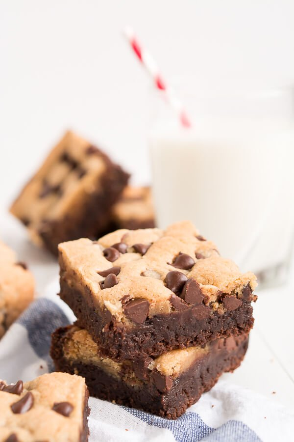 cookie brownie bars on striped towel next to glass of milk
