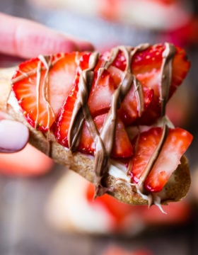 A brown board with brown sugar strawberry crostinis and a chocolate drizzle