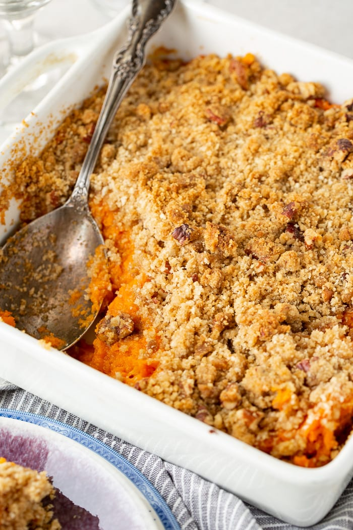 a white casserole dish with a silver spoon lifting out a scoop of sweet potato souffle with brown sugar topping