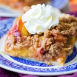 A purple napkin under a vibrant blue china designed dessert plate with a slice of brown sugar peach pie bars with a piped whipped cream dollop on top