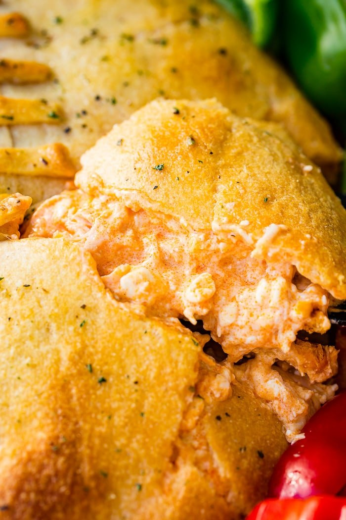 A cookie sheet with crackers, celery, peppers, and a football made out of crescent rolls and stuffed with buffalo chicken dip recipe