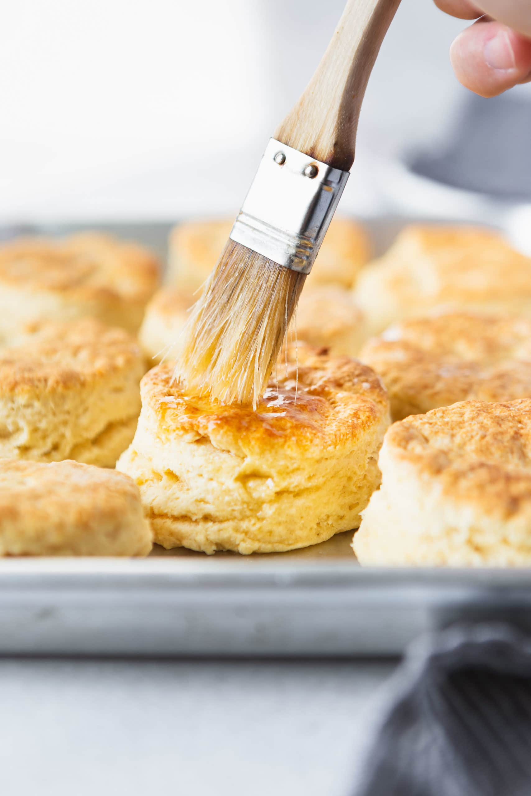 A pan full of golden brown buttermilk biscuits. Butter is being brushed on the top of a biscuit with a pastry brush.
