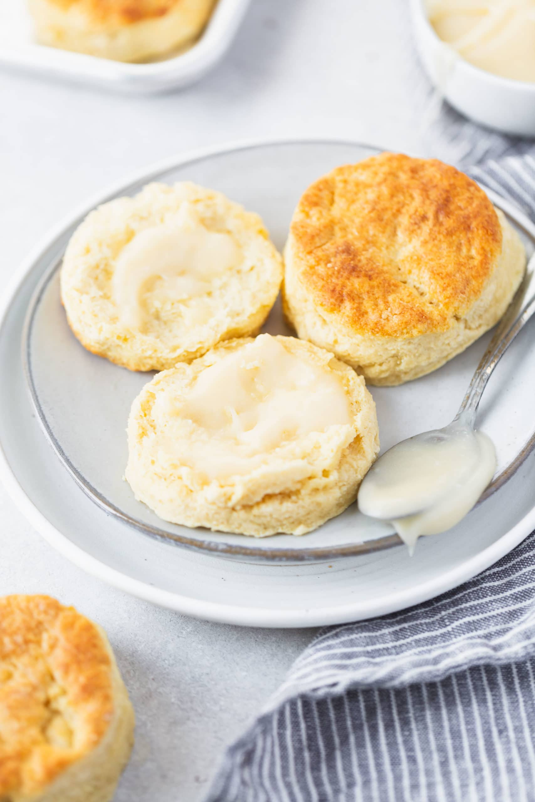 Two buttermilk biscuits on a small white plate. One biscuit is broken in half and has been buttered.