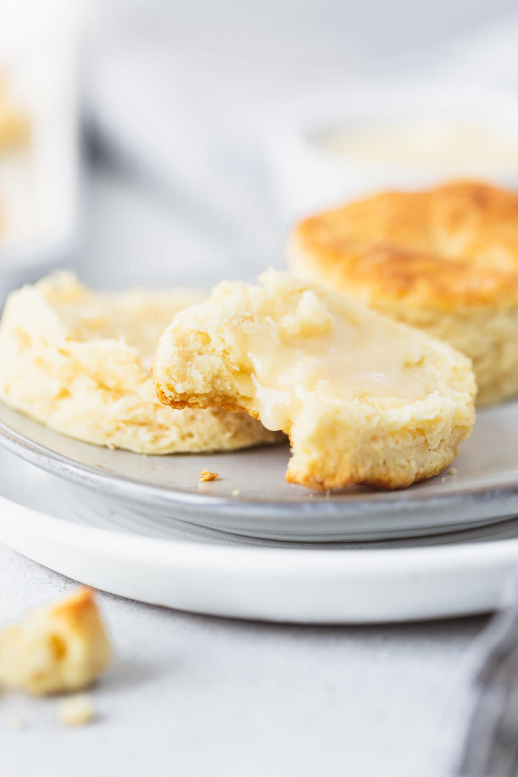 Two buttermilk biscuits on a plate. One biscuit is broken in half and has been spread with honey butter. A bite has been taken from one of the halves.