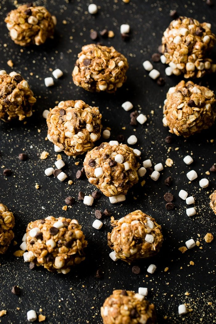 A black board with mini marshmallows, mini chocolate chips, and graham cracker crumbs sprinkled everywhere with protein no bake s'mores energy bites