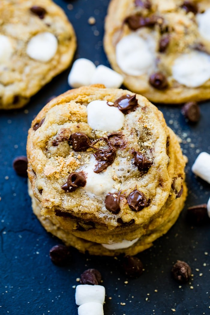 a black background with a stack of s'mores chocolate chip cookies being broken apart with marshmallow stretching out.