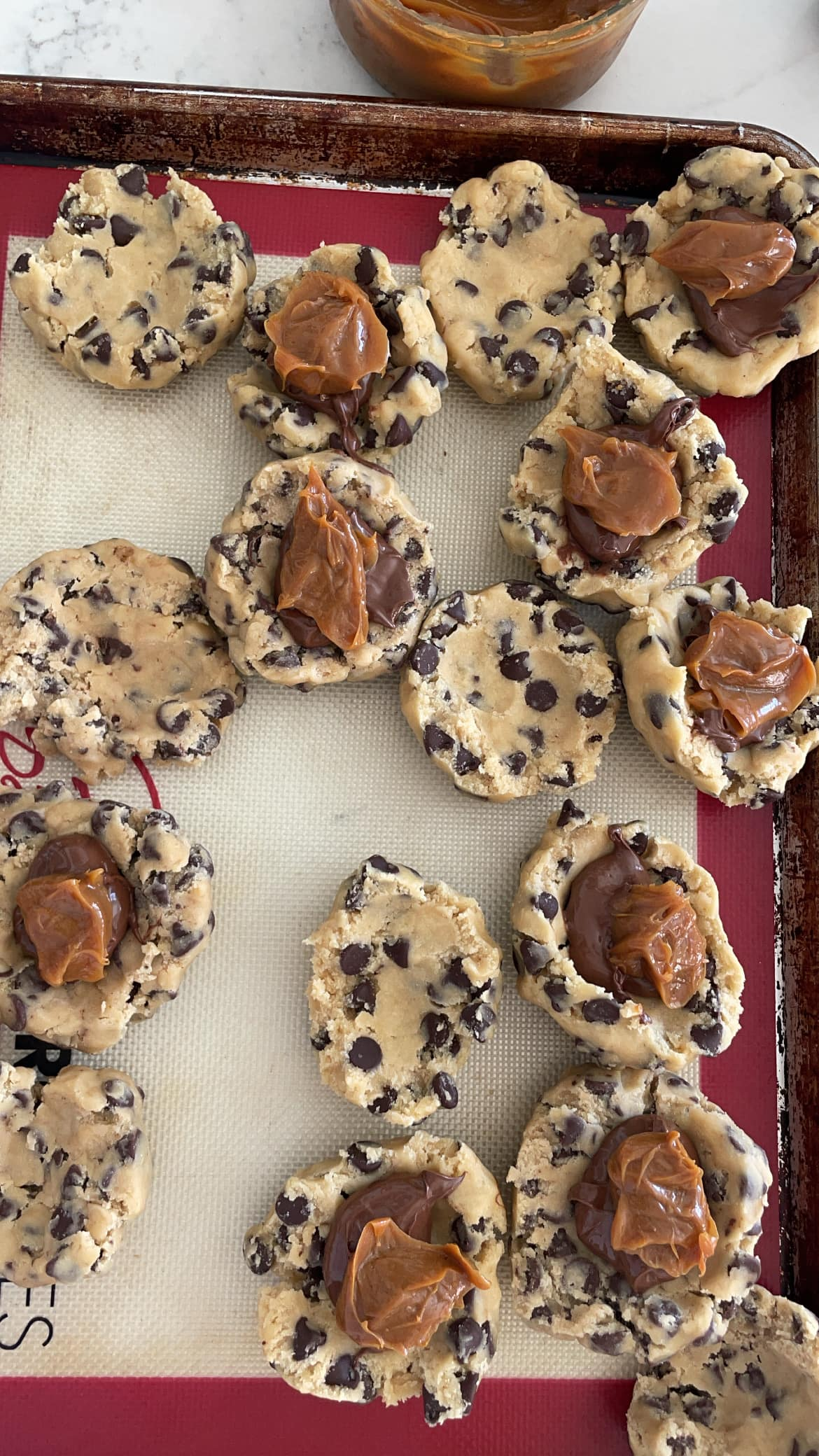 nutella and dulce de leche scooped into chocolate chip cookie dough