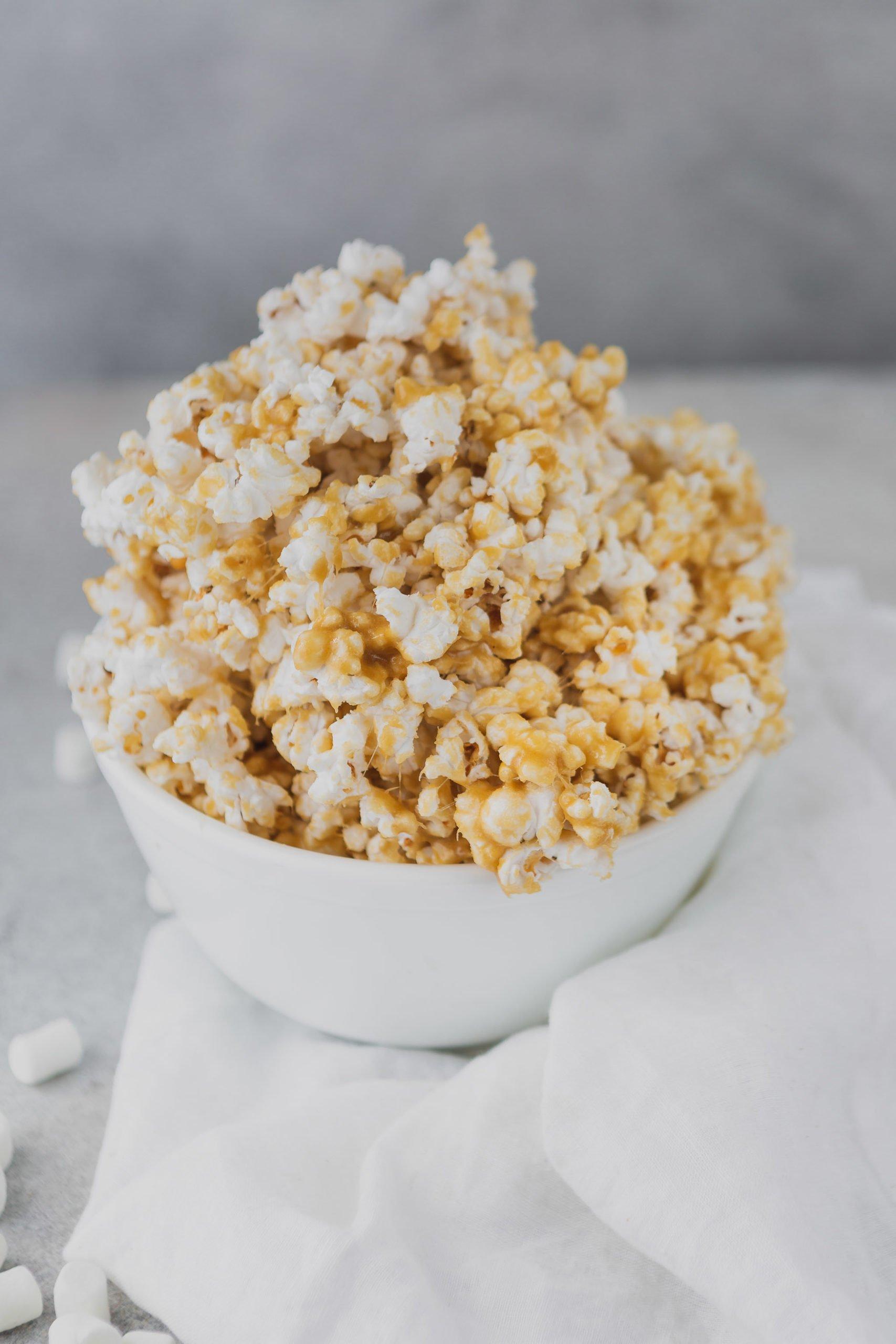 A white bowl heaped full of caramel popcorn.