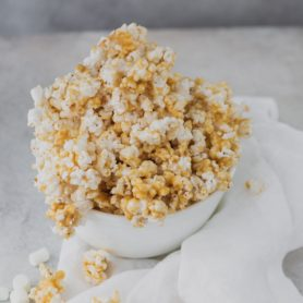 A bowl heaped full of caramel popcorn.
