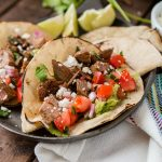 Two authentic carne asada tacos on a serving plate on top of a wooden table.