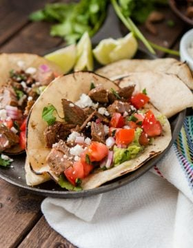 Marinated flank steak makes these authentic carne asada tacos the best we've ever had. Who needs a restaurant or vacation now?!