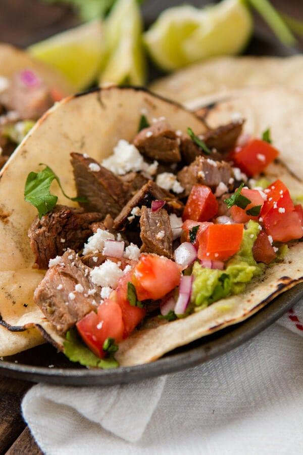 Delicious authentic carne asada taco in a warm corn tortilla with guacamole, red onions and tomatoes on a plate.