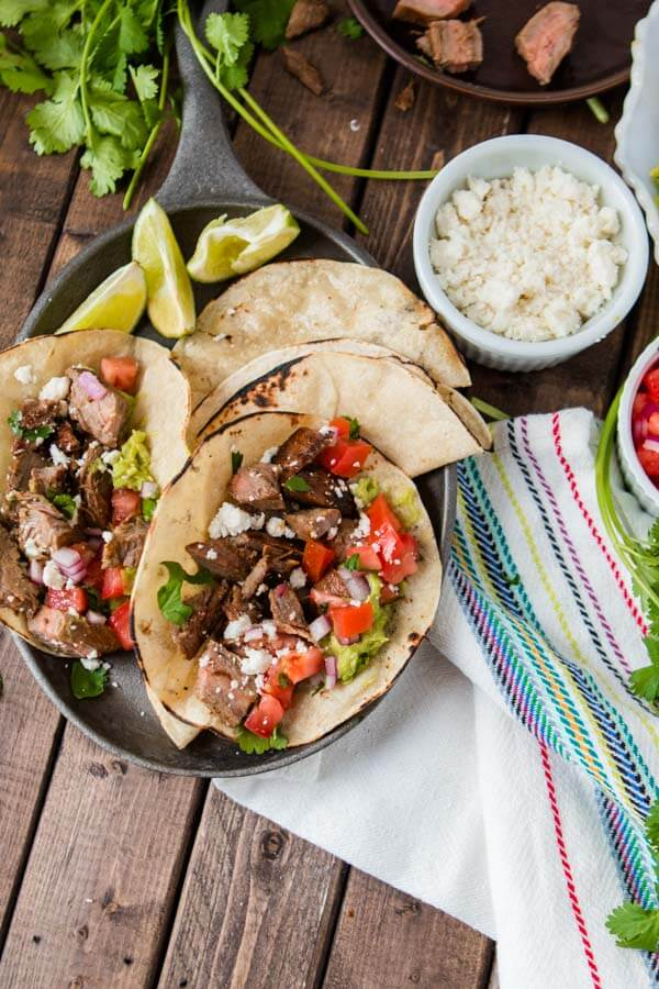 A plate of two delicious carne asada tacos with two tortillas and three slices of lime with a small white bowl of cheese on the side.