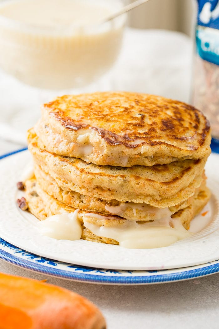 A photo of a stack of golden carrot cake pancakes on a white plate with no syrup added yet.