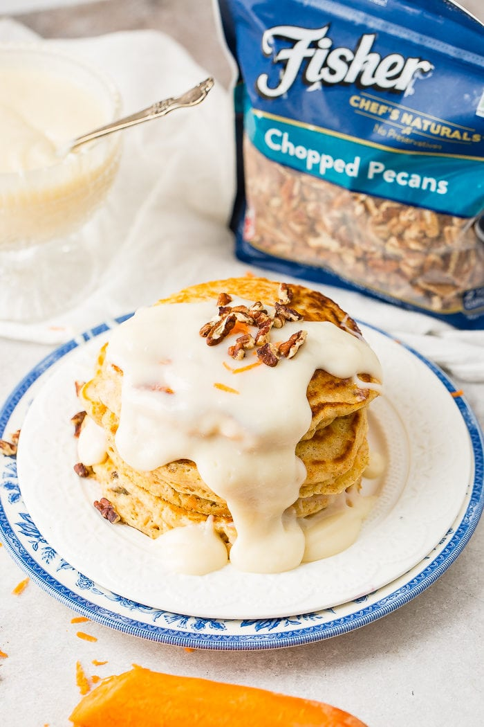 A photo of a stack of four carrot cake pancakes with a thick white cream cheese sauce poured over the top with a few chopped pecans and shredded carrots on top with a bag of Fisher chopped pecans in the background.