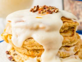 A photo of a stack of four carrot cake pancakes with a thick white cream cheese sauce poured over the top with a few chopped pecans and shredded carrots on top.
