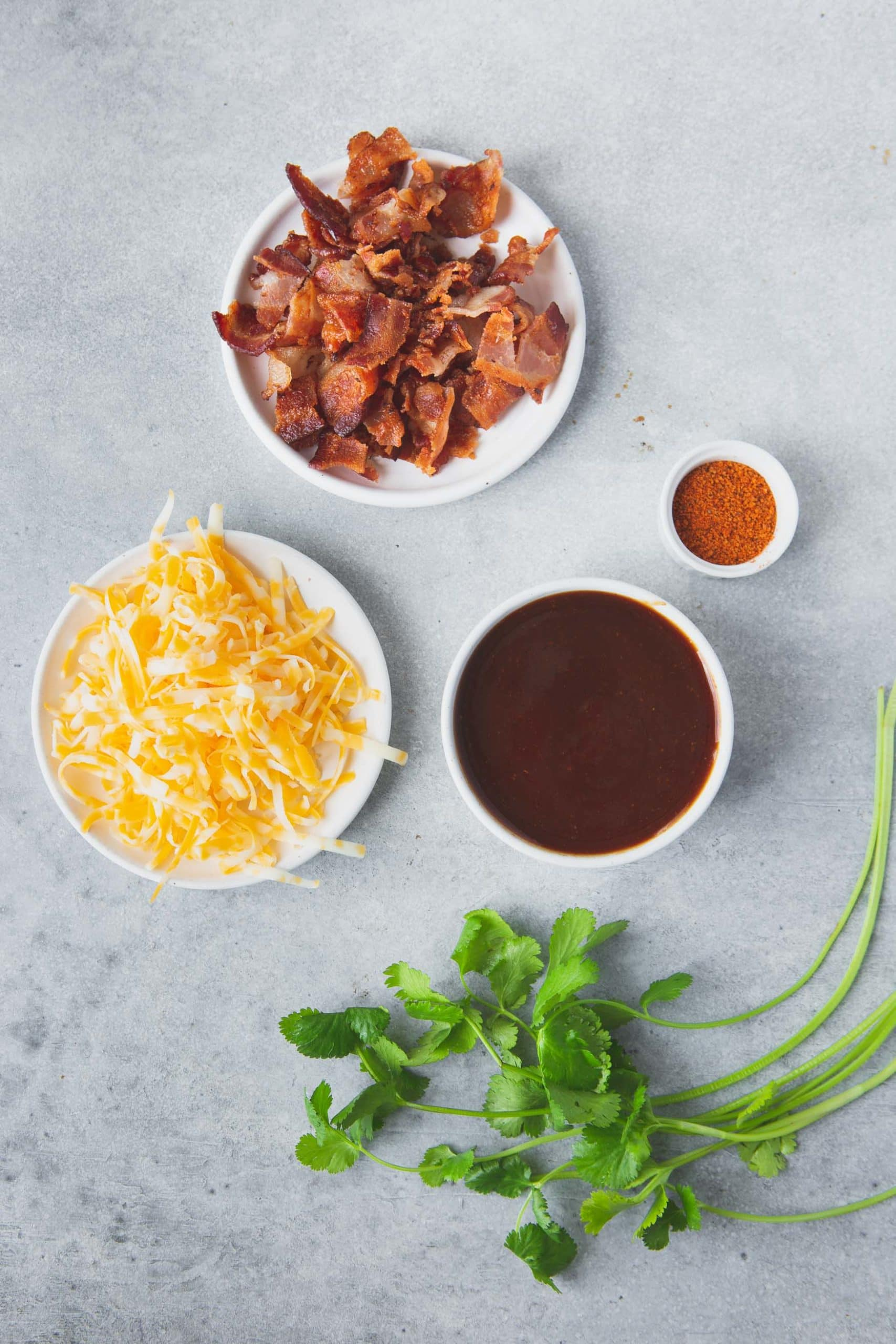 Containers of ingredients for cheesy bbq chicken with bacon. The bowls contain cheese, bbq sauce, bacon and spices.