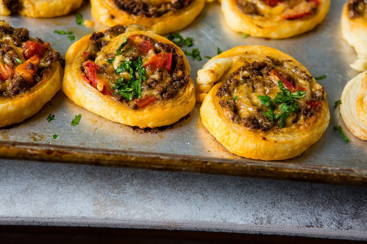 Oh Taco Pinwheels, I can't stop, wont stop!! All you need is puff pastry, taco meat, tomatoes and cheese plus a few bowls of toppings like guacamole! ohsweetbasil.com