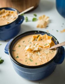 Cheesy Southwestern Chicken Tortilla Soup in a small blue bowl with a silver spoon.