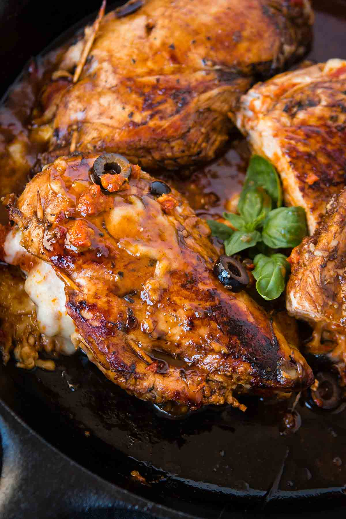 Looking for a quick and easy healthy dinner recipe? We've been loving this Cheesy Stuffed Mediterranean Chicken. It's full of sun dried tomatoes, olives and cheese! This chicken is first put into a delicious balsamic marinade and then stuffed with sun dried tomato pesto, cheese, spinach and olives! ohsweetbasil.com