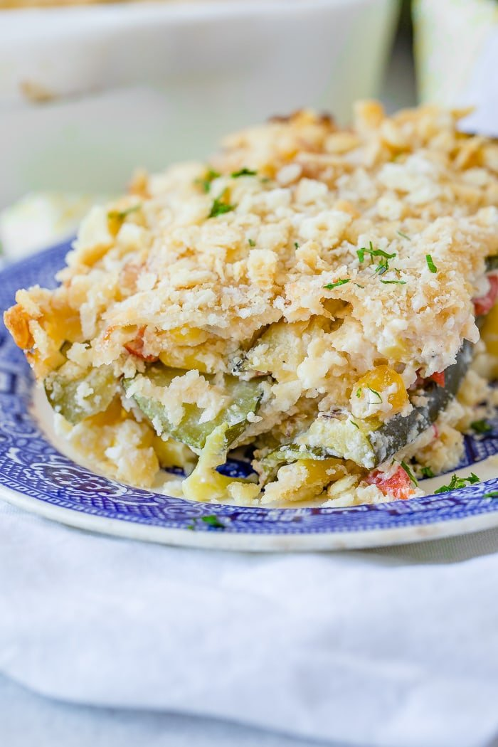 a slice of layered cheesy zucchini corn casserole on a blue china plate with peppers, corn, zucchini, cheese and buttered crackers