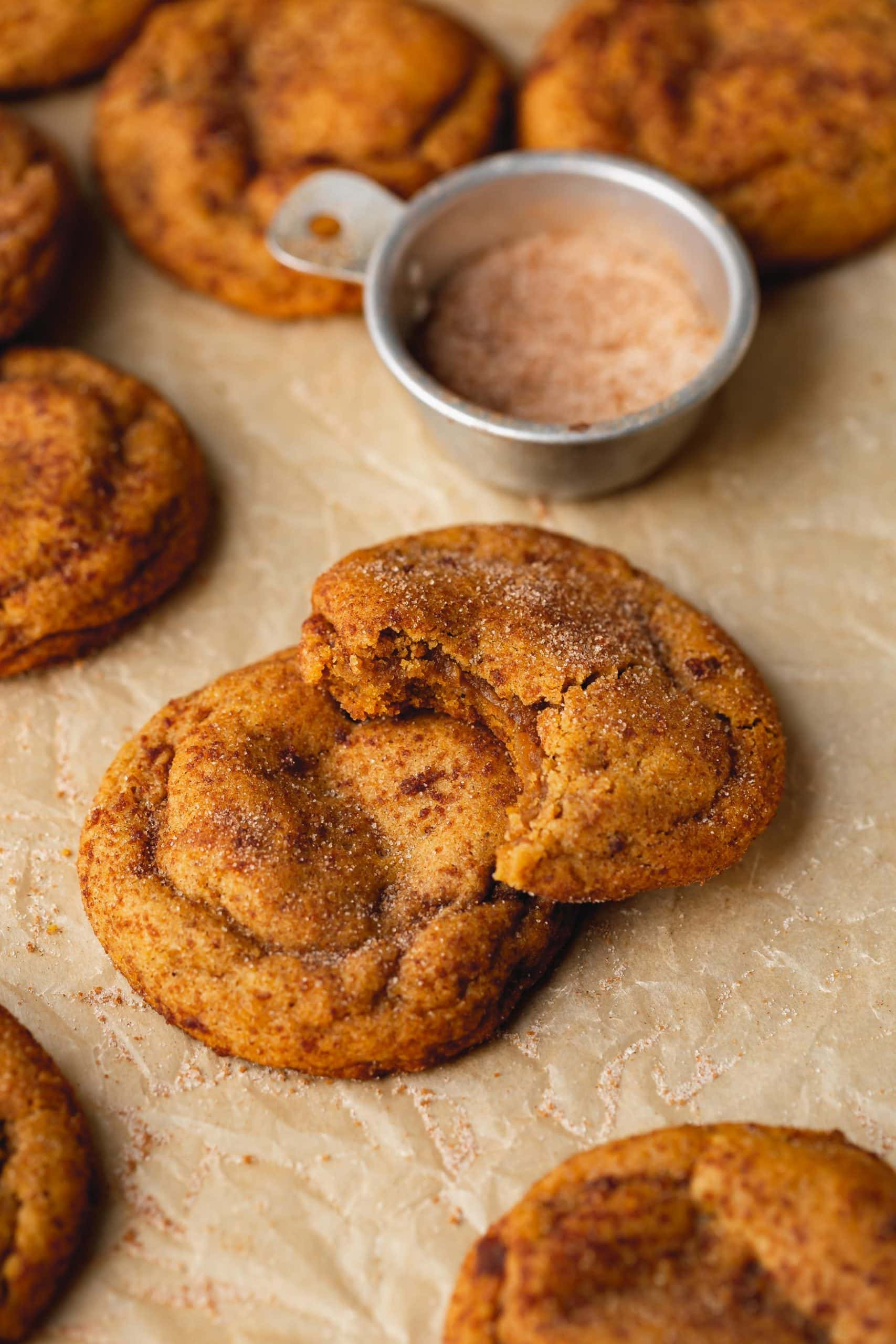 Two chewy pumpkin cookies stacked on top of each other. The cookie on top has a bite taken out of it and there is another cookie and a container of cinnamon sugar in the background.