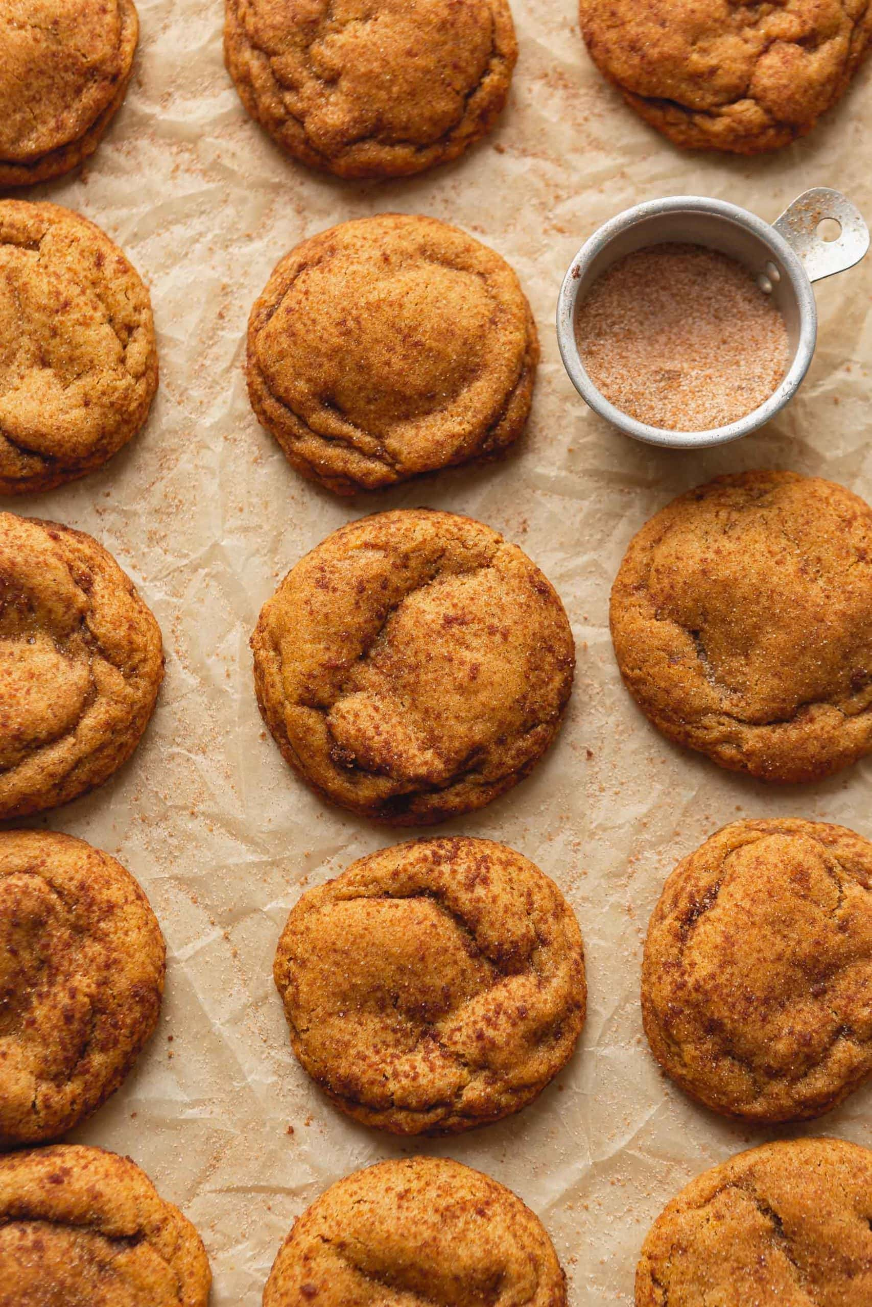 Three rows of chewy pumpkin cookies with a small bowl of cinnamon sugar. The cookies are baked and look soft and chewy.