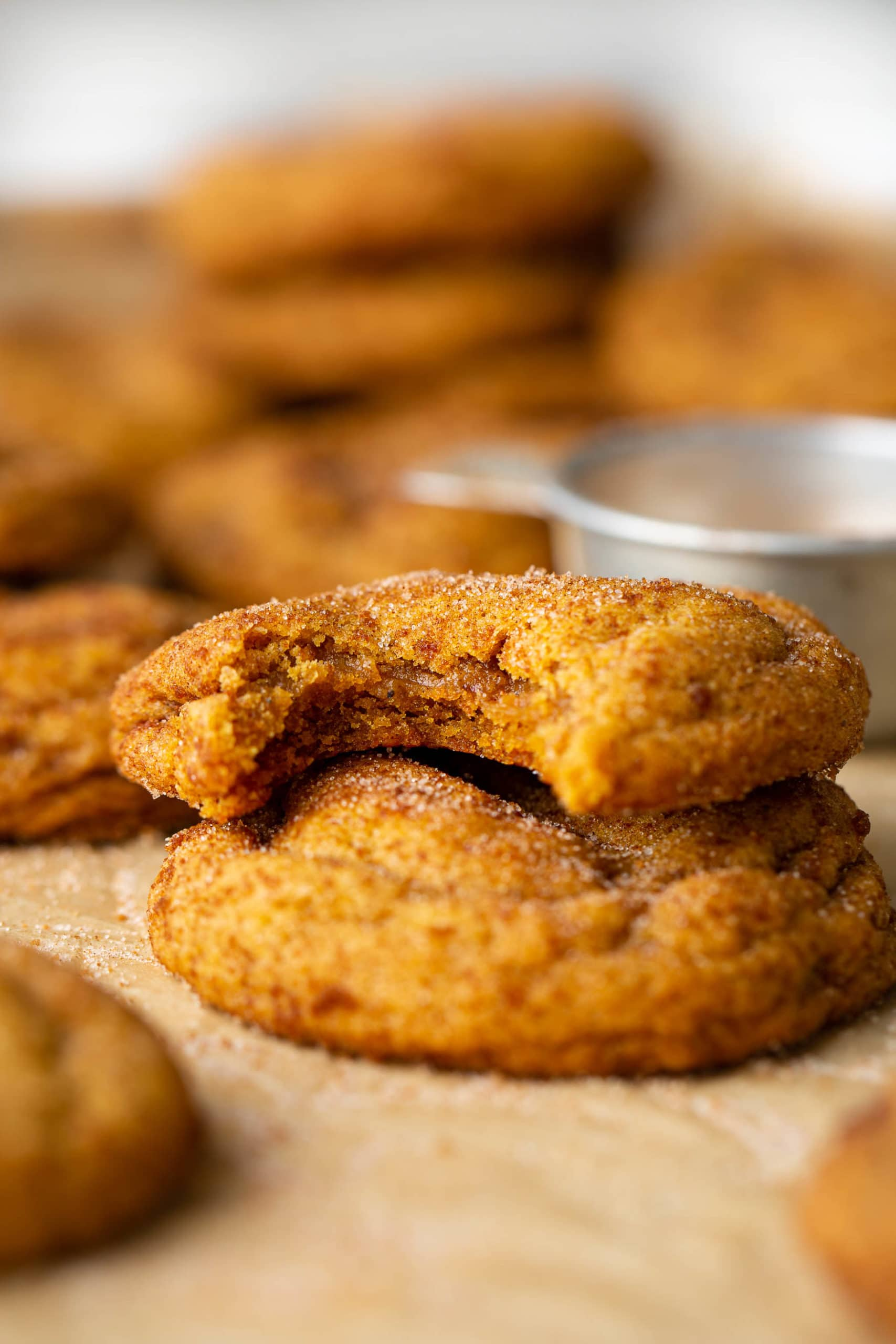 Two chewy pumpkin cookies stacked on top of each other. The top on has a bite taken out of it. They are topped with brown sugar and cinnamon.