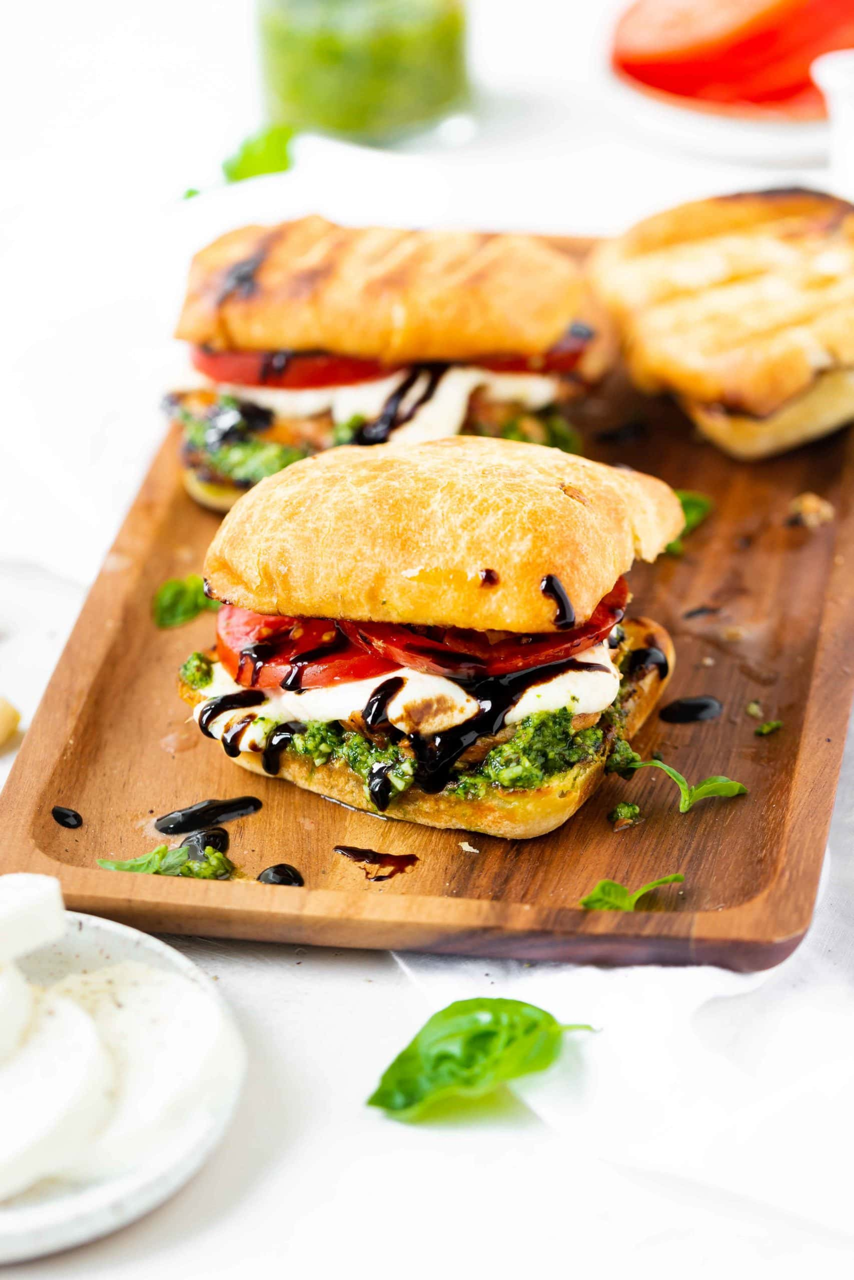a photo of three chicken caprese sandwiches sitting on a wooden rectangular serving tray.