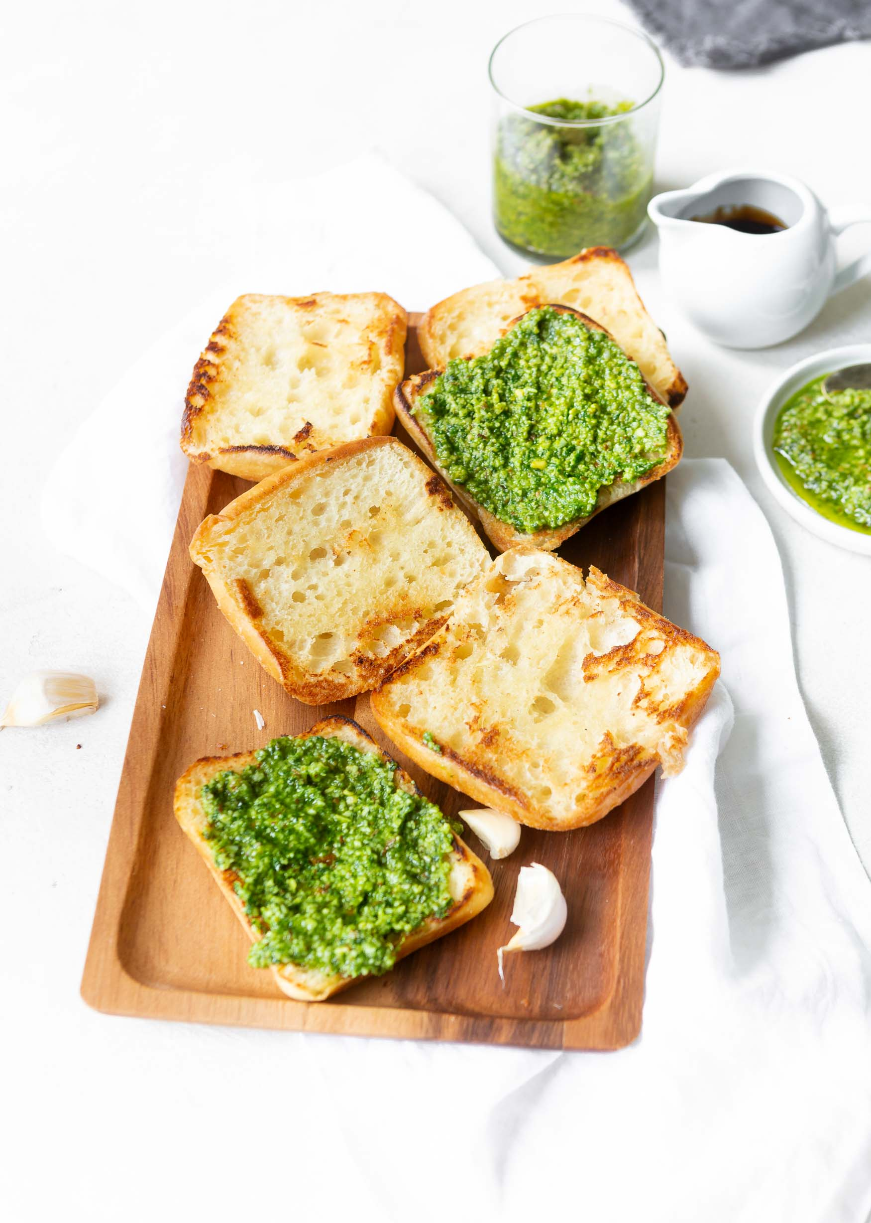 a photo of 3 ciabatta rolls sliced in half and toasted sitting face up on a wooden serving tray and 2 of the 6 slices have pesto spread on them.
