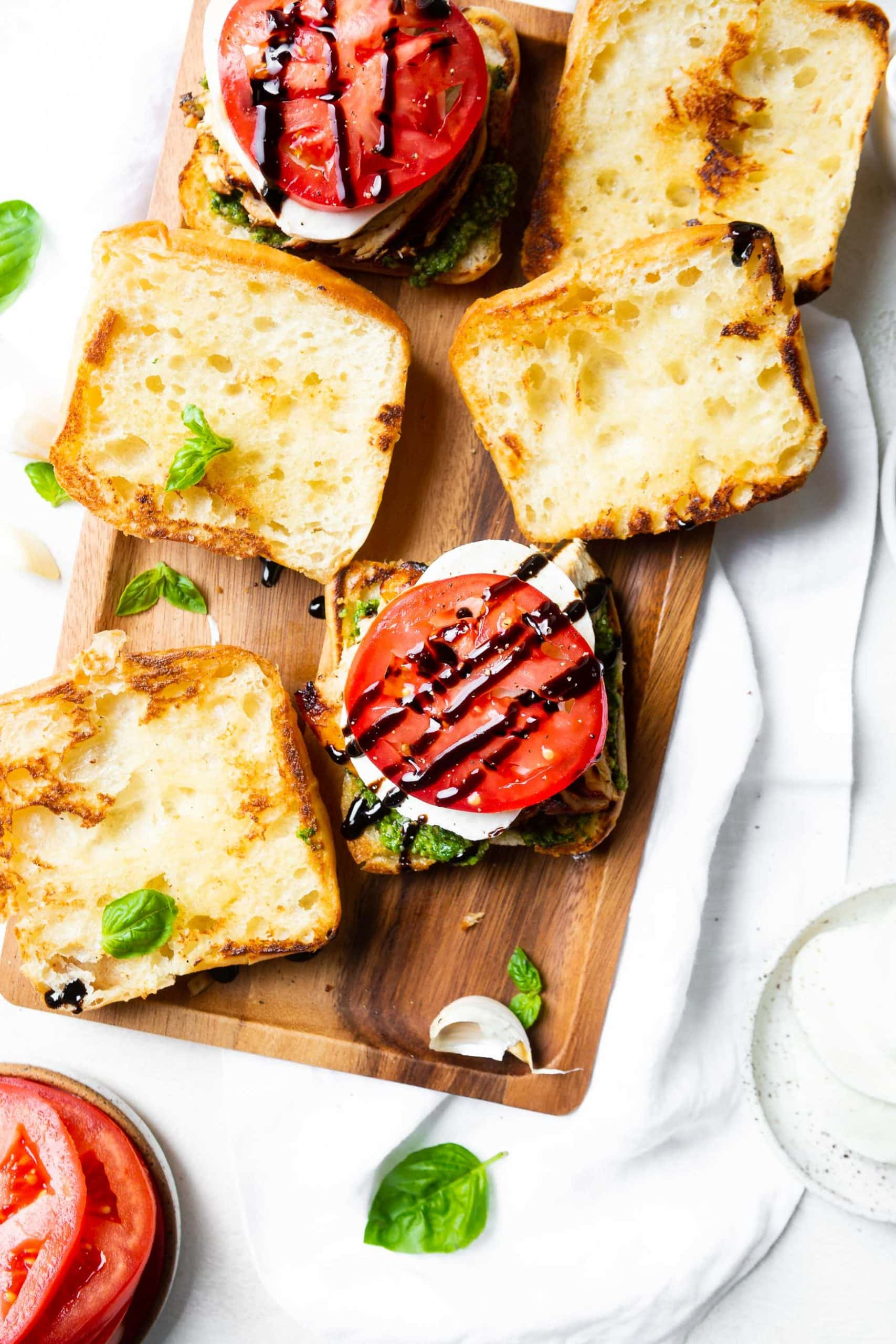 a photo of a ciabatta bun topped with pesto, fresh mozzarella, a tomato slice and a balsamic glaze with the top bun of the sandwich sitting next to it.