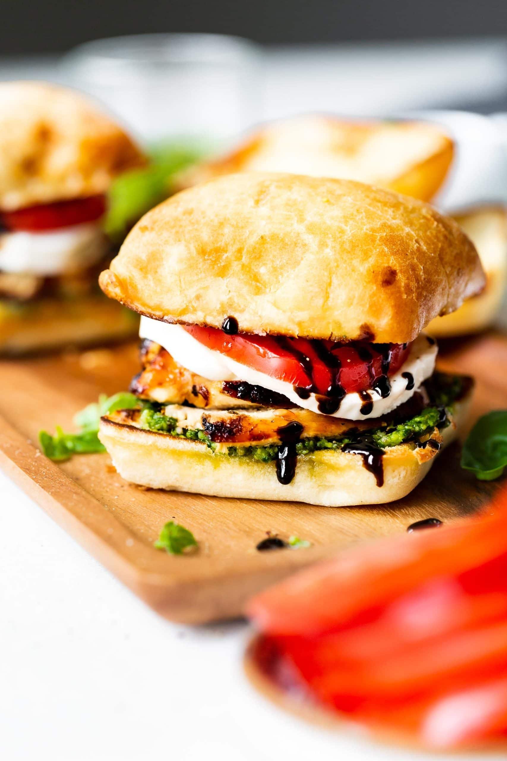 a photo of a chicken caprese sandwich on a ciabatta roll with a layer of pesto, chicken, fresh mozzarella, tomato and balsamic glaze.