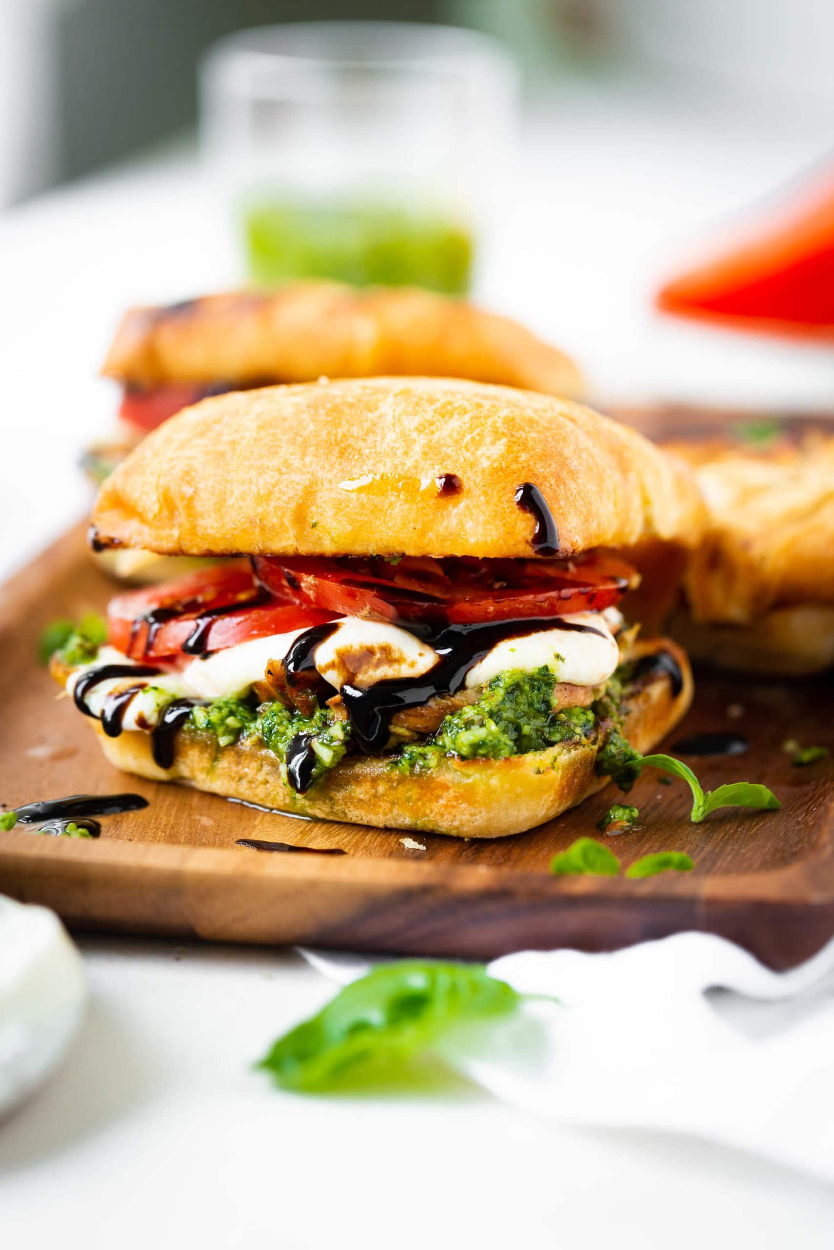 a photo of a chicken caprese sandwich completely assembled sitting on a wooden serving tray. The sandwich has pesto, fresh mozzarella, tomato, chicken, and balsamic glaze all on a toasted ciabatta bun.