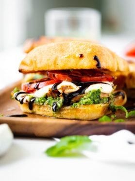 a photo of a chicken caprese sandwich on a ciabatta bun with tomato, fresh mozzarella, pesto and balsamic glaze.