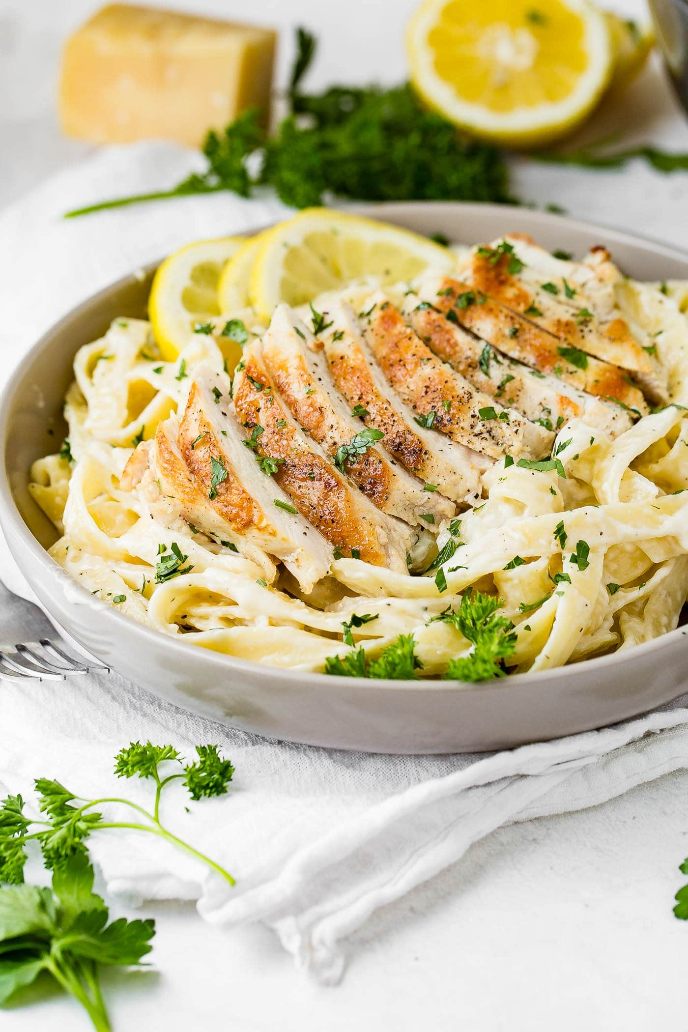 Serving plate filled with chicken fettuccine alfredo.  Place chicken strips over pasta and sprinkle with fresh parsley.